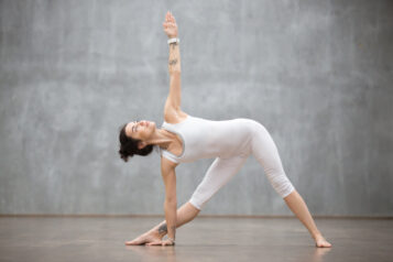 Profile portrait of beautiful young woman wearing white sportswear working out against grey wall, doing yoga or pilates exercise. Standing in Utthita Trikonasana, extended triangle pose.